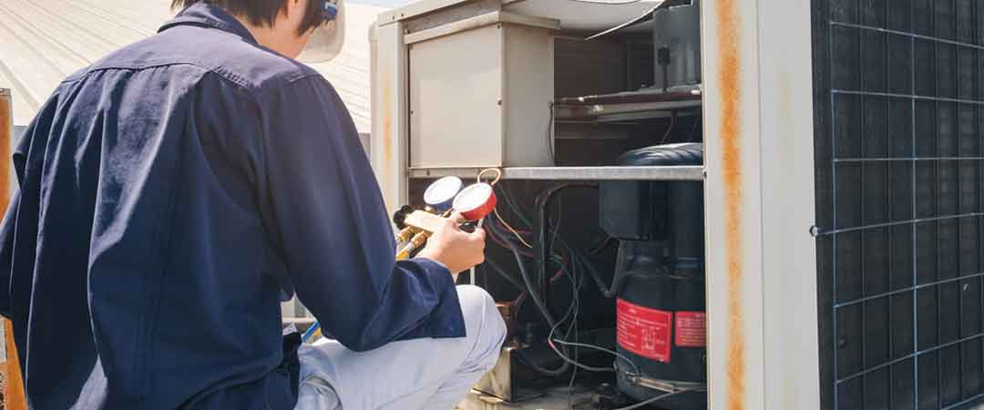Tech checking air conditioner compressor