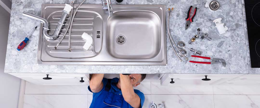 Repairman under a sink working on a garbage disposal