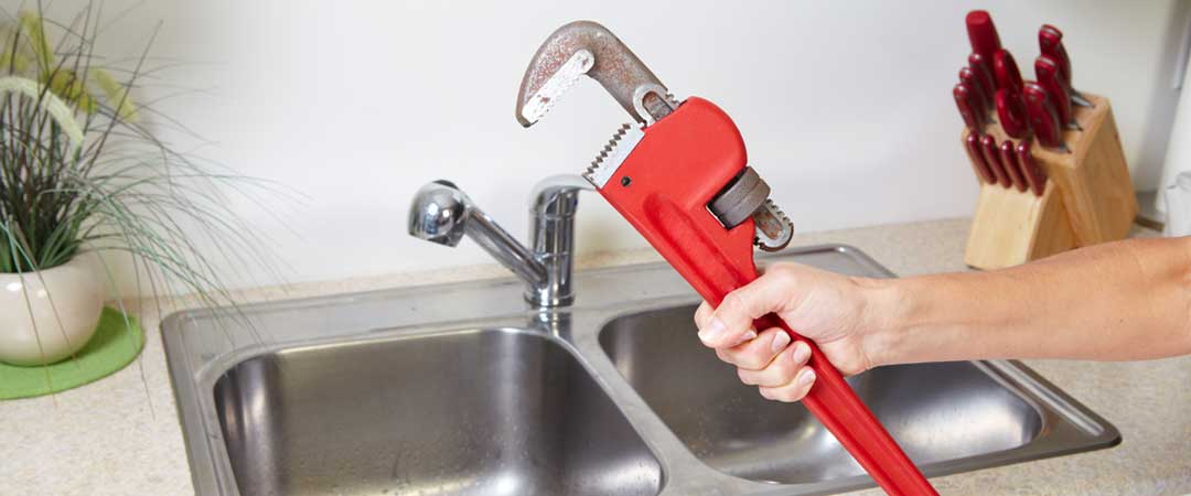 Kitchen sink with a man holding a pipe wrench