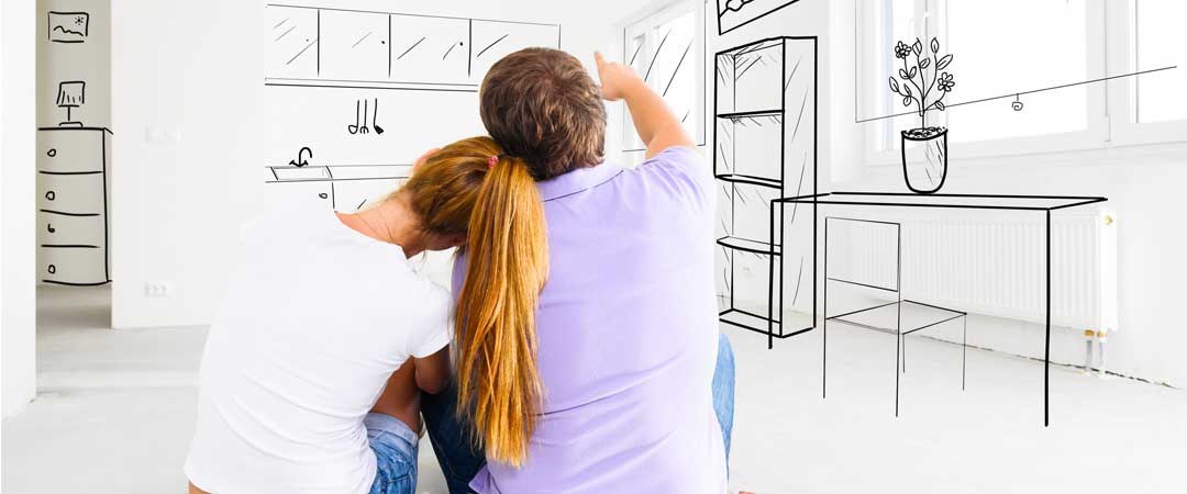 Couple sitting on kitchen floor planning their sink area